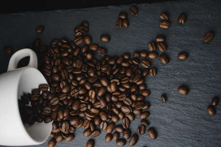 Flat lay coffee bean spilt from white cup on a stone slate plate, dark background. Copy space concept Stock fotó