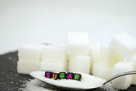 Sugar block letters in crossword and sugar pile on a spoon