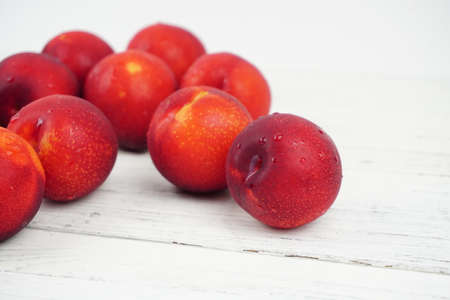 Plums ripe fresh on the wood texture background