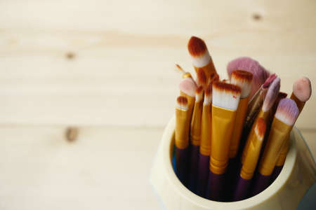 Make up brushes in wooden box. Copy Space Concept