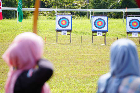 Archery wearing traditional dress target ring and out of focus archer with a bow in the foreground during an archery competition