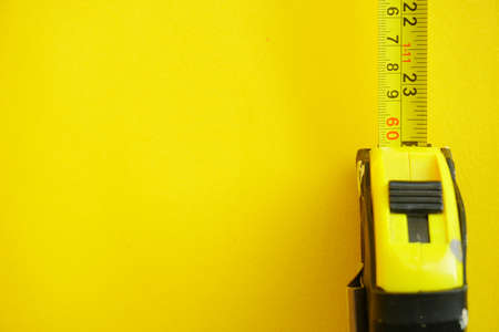 Close up ellow Measuring Tape over bright yellow background. Selective Focus, Copy Space