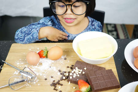 Sweet little cute girl is learning how to make a cake, in the home kitchen, Family concept,