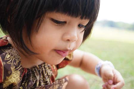Cute litle Young Girl Wearing Batik Design Dress on a park. Selected Focus. Stock Photo
