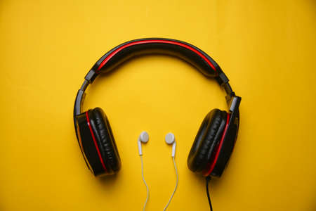 Black Gaming headphones on yellow background. Music concept.