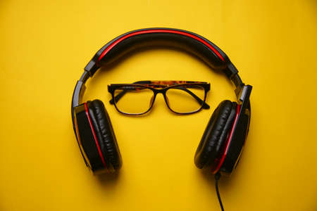 Black Gaming headphones with a glass represent a person on yellow background. Music concept.