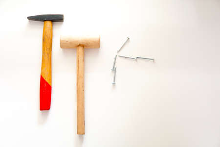 wooden hammer and metal hammer with iron nails on white background.