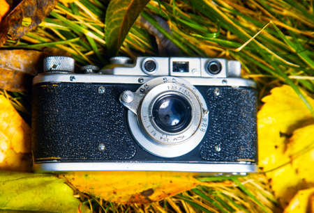Retro photo camera on ground with leafs and grass
