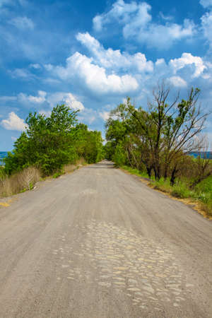 Spring landscape with road, trees and clouds on the blue sky Stock Photo