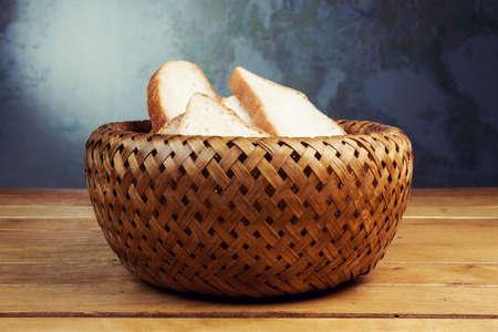 breadbasket: Slices of bread in wicker breadbasket on wooden table