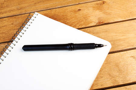Blank notepad with blank pen on wooden table