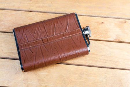 Brown hip flask on the wooden table