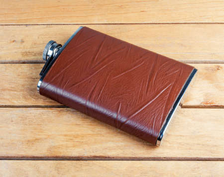 hip flask: Brown hip flask on the wooden table