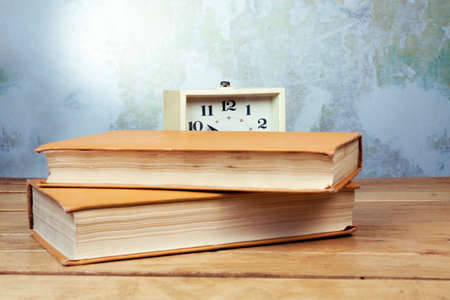 Old alarm clock with books on a wooden table