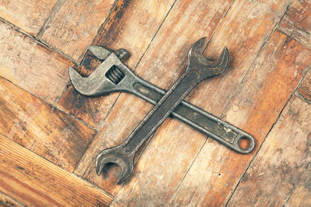 adjustable spanner: Old crossed adjustable spanner wrench on wooden floor Stock Photo