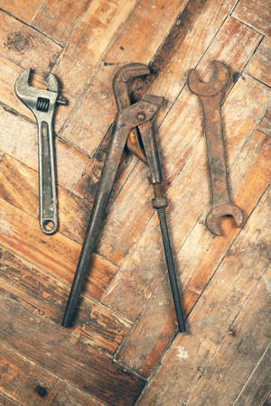 pipe wrench: Set of old adjustable spanner, pipe wrench and open-end wrench on wooden floor Stock Photo
