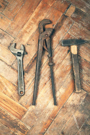 adjustable spanner: Set of old adjustable spanner, pipe wrench and hammer on wooden floor