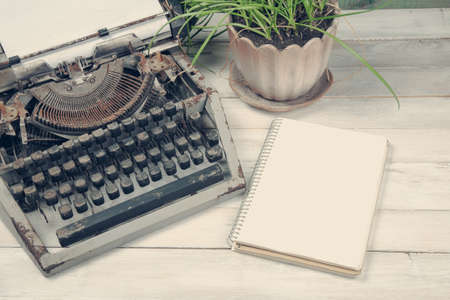 typewrite: Dirty vintage typewrite with plant and blank notebook on the wooden table