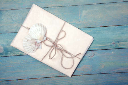 Paper wrapped package with two sea shells on white wooden background Stock Photo