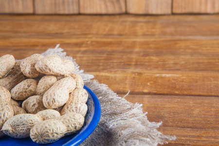 Not peeled peanuts in blue plate on sackcloth on wooden background Stock Photo