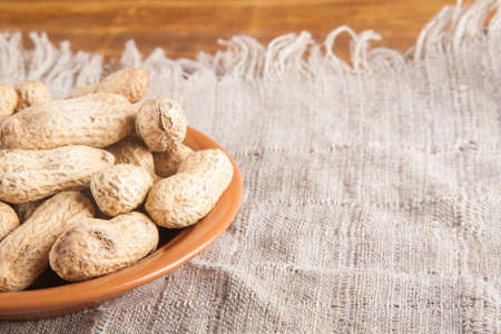 Not peeled peanuts in the plate on sackcloth on wooden background Stock Photo