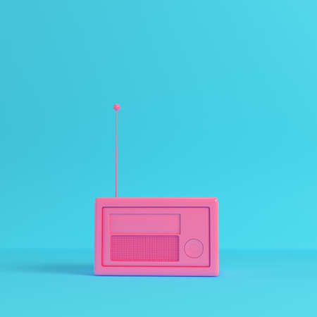 Pink retro styled radio on bright blue background in pastel colors.