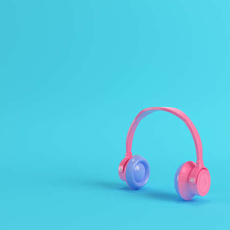 Pink headphones on bright blue background in pastel colors. Minimalism concept. 3d render