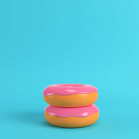 Two donuts with pink glaze on bright blue background in pastel colors. Minimalism concept. 3d render Zdjęcie Seryjne