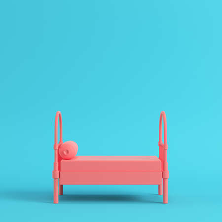 Pink single bed with pillow on bright blue background in pastel colors. Minimalism concept. 3d render