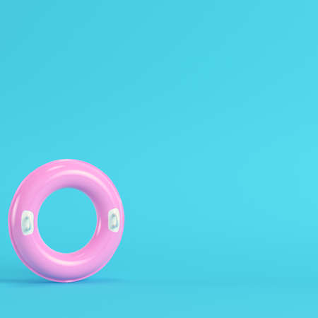 Pink inflatable ring on bright blue background in pastel colors. Minimalism concept. 3d render Foto de archivo