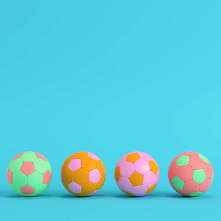 Four colorful soccer balls on bright blue background in pastel colors. Minimalism concept. 3d render