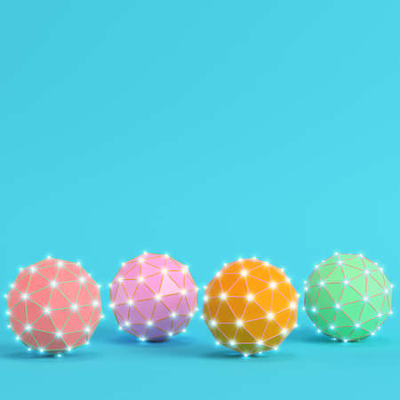 Four colorful low poly abstract glowing spheres on bright blue background in pastel colors. Minimalism concept. 3d render Imagens