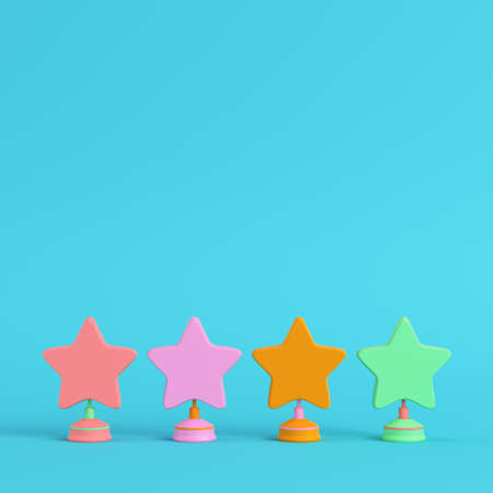 Four colorful stars with stands on bright blue background in pastel colors. Minimalism concept. 3d render Imagens