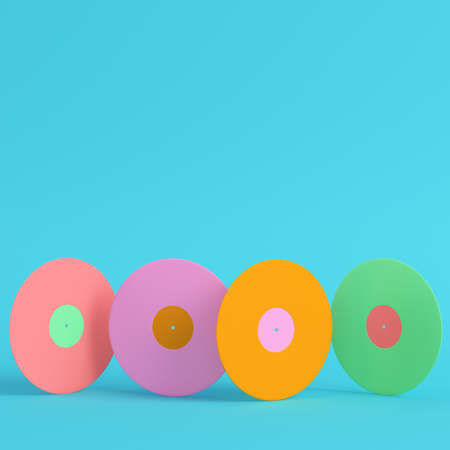 Four colorful vinyl records on bright blue background in pastel colors. Minimalism concept. 3d render