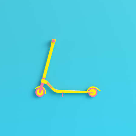 Yellow kick scooter on bright blue background in pastel colors. Minimalism concept