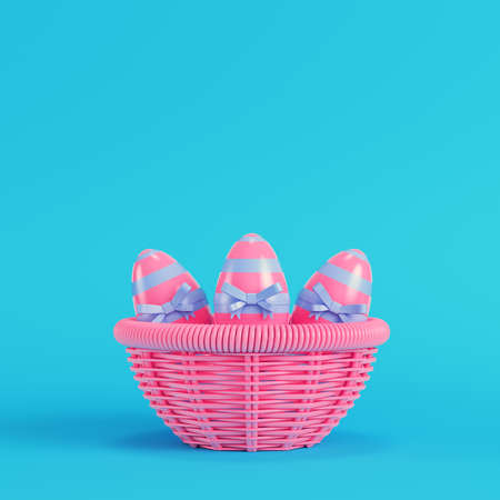Pink easter eggs with bow in a wicker basket on bright blue background in pastel colors. Minimalism concept. 3d render