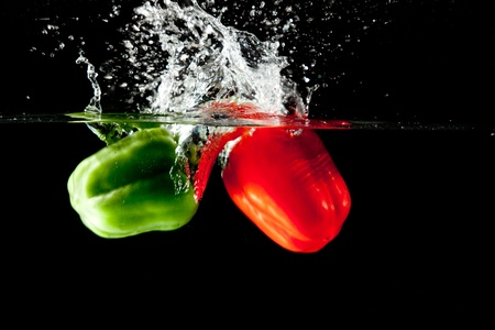 Red and green pepper drop in a water tank creating a splash