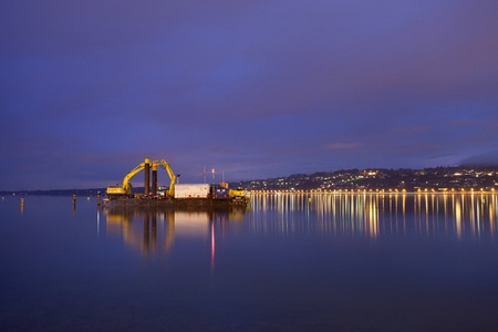 dredging tools: January 8th, 2012 Geneva, Switzerland. A hydraulic excavator machine in the middle of Lake Geneva, in the morning before a work day.