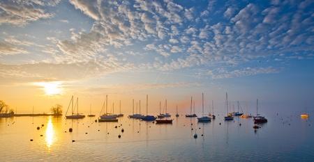Sunrise at Lake Geneva, Switzerland with sailboats and yachts