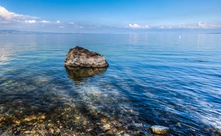 A stone half submerged in Lake Geneva, Switzerland  photo