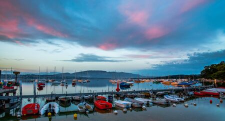 Small boats at a pier and colorful sunrise clouds at a small bay at Lake Geneva, Switzerland  photo