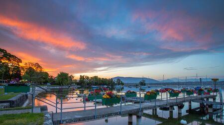 Small boats at a pier and colorful sunrise clouds at a small bay at Lake Geneva, Switzerland  photo