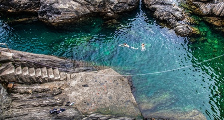 liguria: Manarola, Cinque Terre, Liguria. August 6, 2012. People swimming in a lagoon in Manarola.