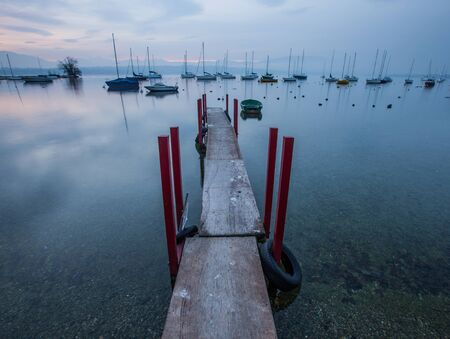 A wooden jetty and boats at Creux de Genthod, Lake Geneva at sunrise  photo