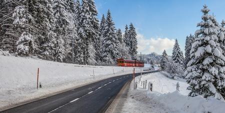 A red train in a Swiss winter landscape