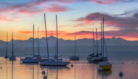 Sonnenaufgang und Segelboote an einer kleinen Bucht im See Genf, Schweiz