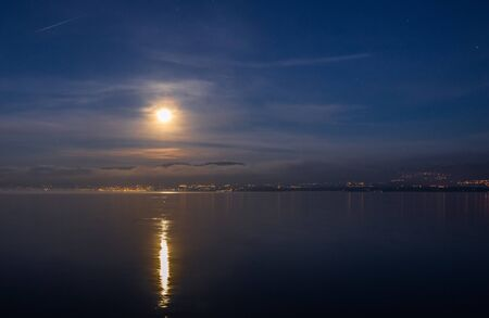 jura: Full moon over Jura mountain range and Lake Geneva in a winter dawn Stock Photo