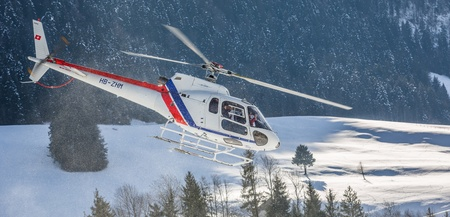 oex: Chateau de Oex, Switzerland, 26th January 2013. A helicopter flying at a snow field at the 35th International Hot Air Balloon festival. It is being held from 26th January to 3rd February 2013.