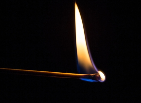 dangerous ideas: Burning match with a black background. Stock Photo