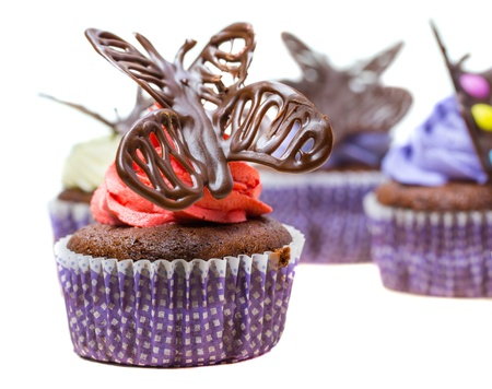 Chocolate butterfly decorated cupcakes on white background photo